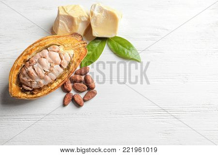 Cut cocoa pod, beans and butter on light background