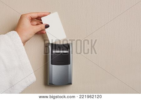 Hand inserting key card in electronic lock. Woman in white bathrobe opening hotel room door. Privacy, security, personal identification concept, copy space poster