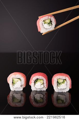 Set of three sushi rolls with fish, vegetables and cheese, chopsticks taking one piece. Traditional japanese food on black glass with reflection, copy space. Asian restaurant meals delivery