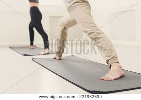 Unrecognizable man and woman warmup stretching legs training at white background indoors. Young couple make aerobics exercise, copy space