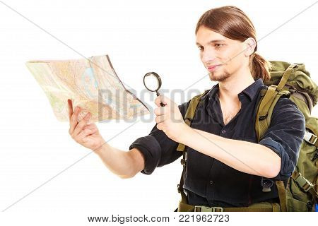 Man tourist backpacker reading map with magnifying glass loupe. Young guy hiker searching looking for direction guide. Male backpacking. Summer vacation travel. Isolated on white background.