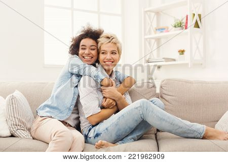Two female friends embracing each other at home. Happy women hugging, success, unity and togetherness concept, copy space