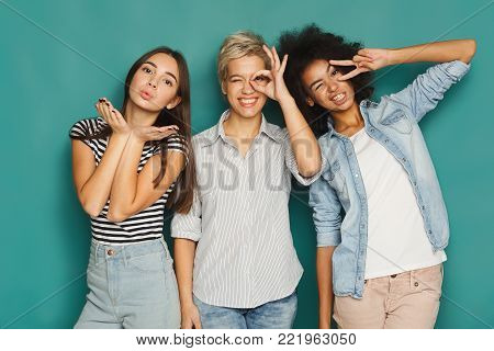 Happy female friends having fun at blue background. Three young women posing, showing different signs and laughing, slumber party, copy space
