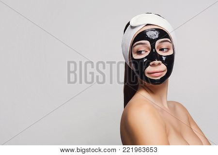 Skin care. Portrait of young girl with black mask on face. Purifying spa treatment, white studio background, copy space