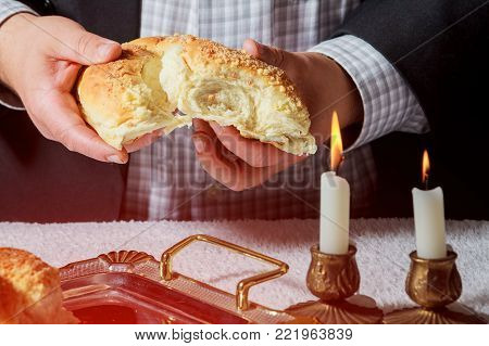 Sabbath kiddush ceremony composition with two wax candles in candlesticks and a traditional sweet fresh loaf of challah bread