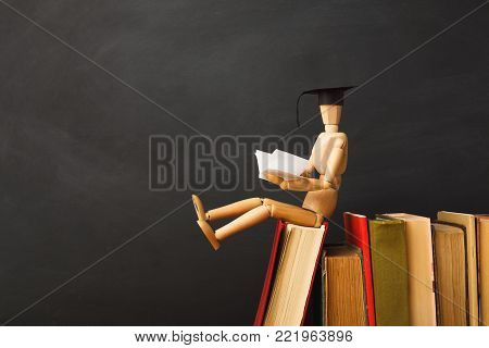 Educational background. Wooden marionette in graduation hat sitting on old books and reading against empty classroom blackboard for copy space, closeup. Back to school concept
