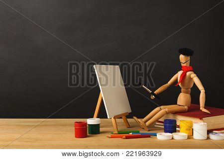Art background. Wooden marionette artist in hat sitting on old book and painting against empty classroom blackboard, copy space. Back to school concept
