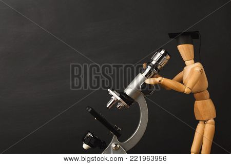 Educational background. Wooden marionette in graduation hat looking in microscope against empty classroom blackboard for copy space. Back to school concept