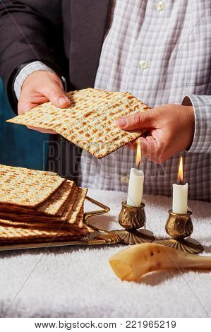 passover matzah is a traditional jewish fresh sabbath bread loaf. Hands of men keep bread and two wax candles in candlesticks.