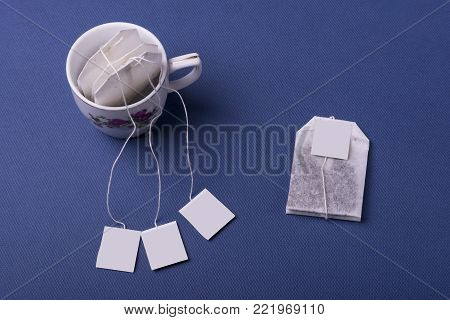 Porcelain white cup tea with three teabags on dark blue background. top view studio shot