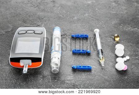 Digital glucometer, lancet pen, syringe and medicaments on grey background. Diabetes management