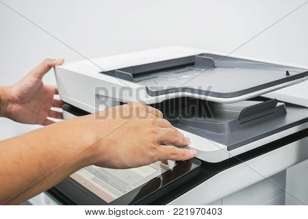 close up man use multi functional printer in office for work
