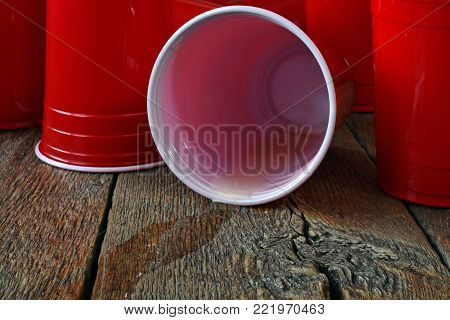 A close up image of beer spilling out of red plastic cups.