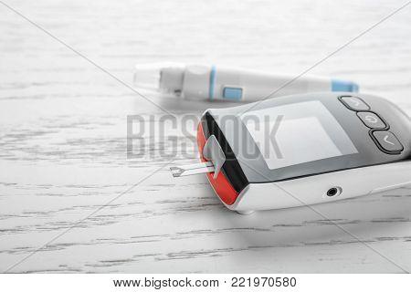 Digital glucometer and lancet pen on light background. Diabetes management