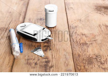 Digital glucometer, lancet pen and medicaments on wooden background. Diabetes management