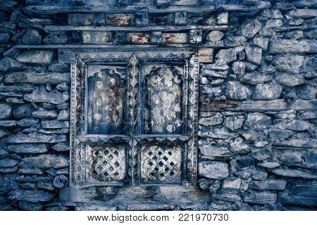 Ancient stone wall with the stylish window with wood carving. Perfect vintage background in blue tints. Artistic retouching. Ideal for retro style collages and illustrations.
