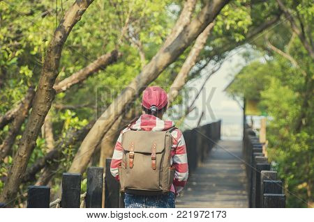 Beautiful woman of a student working on the bridge  looking mangrove forest and relaxing on a park background.Travel concept.