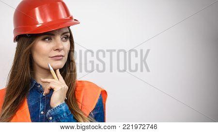 Woman construction worker builder structural engineerin in orange vest red hard helmet. Safety in industrial work. Studio shot