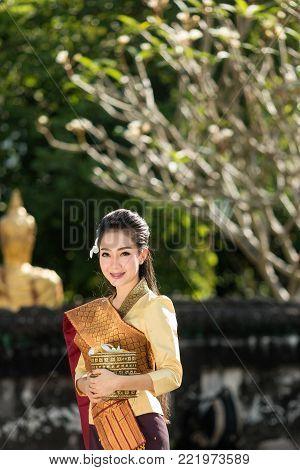 Beautiful Laos girl in Laos costume, Asian woman wearing traditional Laos culture standing at temple at countryside Laos.