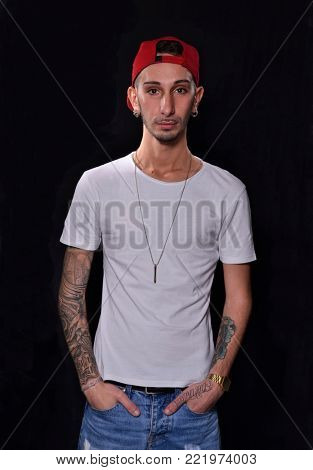 Tattoo young man portrait wearing white shirt on black background.