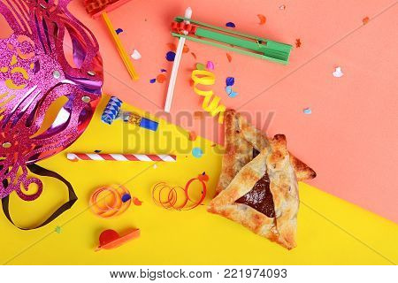 Top view of Purim background with carnival mask, party costume and cookies. Purim celebration concept
