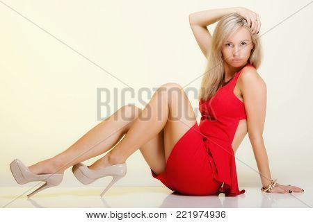 Fashion woman in full length. Girl in fashionable red dress posing. Studio shot yellow background