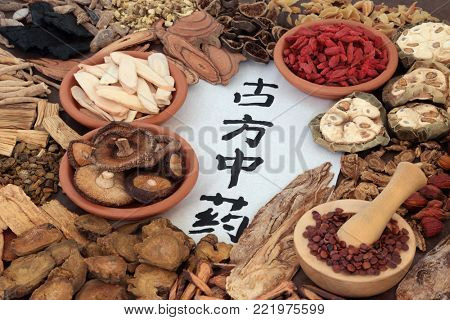 Chinese herbal medicine with selection of herbs and calligraphy script on rice paper. Translation reads as traditional ancient chinese medicine.