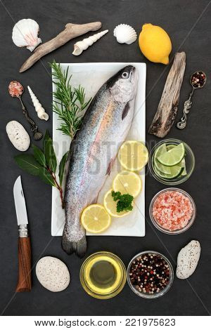 Rainbow trout healthy heart food on crushed ice with rustic knife, herbs, peppercorns, olive oil, himalayan salt, lemon and lime on slate background. High in omega 3 fatty acids and antioxidants.