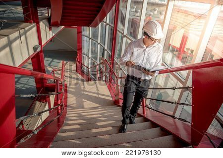 Young Asian Engineer or Architect holding files and architectural drawing wearing personal protective equipment safety helmet at construction site. Civil engineering, Architecture and building concept