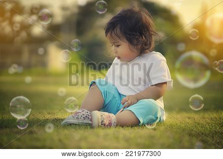 Portrait of sweet asian baby girl sitting on grass in park at sunny day. Healthy happy funny smiling face young adorable  beautiful baby girl. Baby concept.
