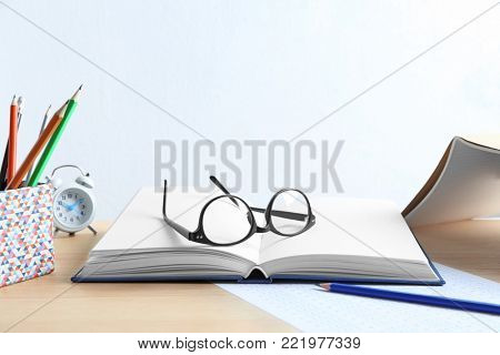 Open notebook with students eyeglasses on table. Revising for exams