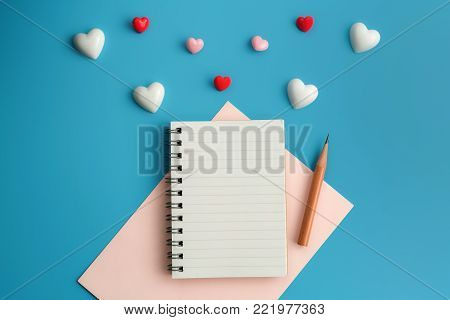 Flat view of love alphabet in the centre of valentines hearts and decoration on red background with copy space. Symbol of love. Happy Valentines Day background.Saint Valentine's Day concept. Can be used for celebrations valentines day.