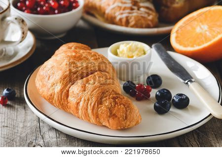 Croissant with fresh berries and butter. Coffee, berries and fruits on background. Concept of continental breakfast. Closeup view