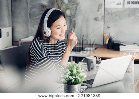 Young asian casual businesswoman arm on desk rest pose with laptop computer and listening music via headphone and think about work ,work at home with relax feeling concept.