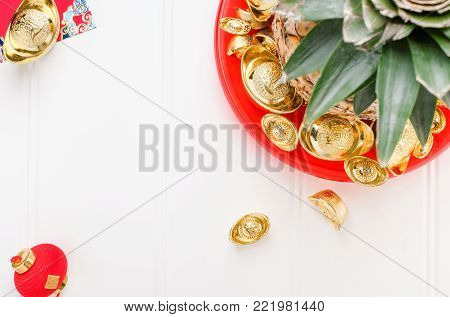 Chinese New year ang pow concept.Top view Pineapple with group of gold ingots in red tray on white wood table.on ingots mean wealthy.