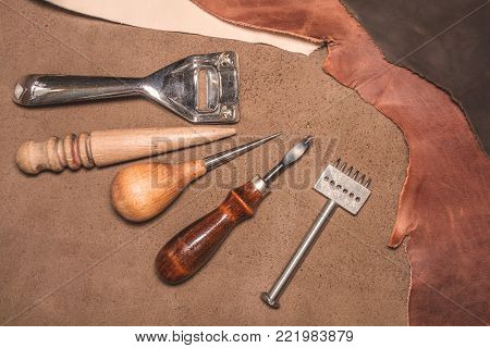 Manufacture of leather goods. Materials and tools for leather production. Beautiful brown pieces of genuine leather and tools for craft.