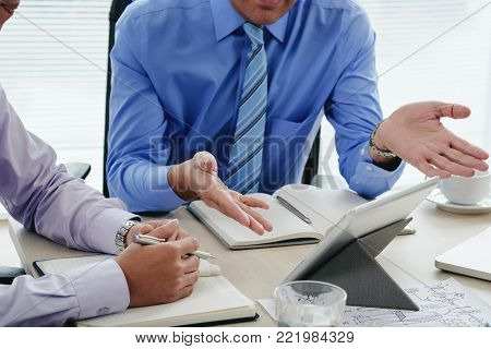 Cropped image of business people dicussing information on digital tablet
