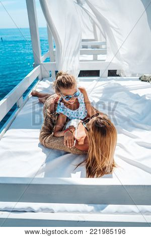 Mom and daughter spend time together on the beach bed