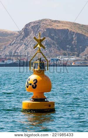 Yellow buoy in the Port of Ensenada in Baja California, Mexico with mountains in the background.