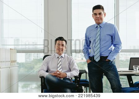 Cheeful middle-aged business people smiling and looking at camera
