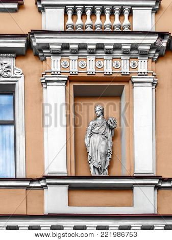 Architectural details balconies, pilasters, arches, rosettes, cornices, busts, a statue in a niche, white patterns on the facade of an ancient building in the center of St. Petersburg on the Griboedova Canal