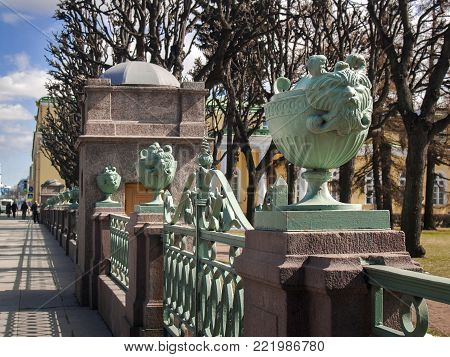 Architectural details in the form of vases with the heads of mythical creatures on the fence of the Tauride Palace on Shpalernaya Street in the city of St. Petersburg in April