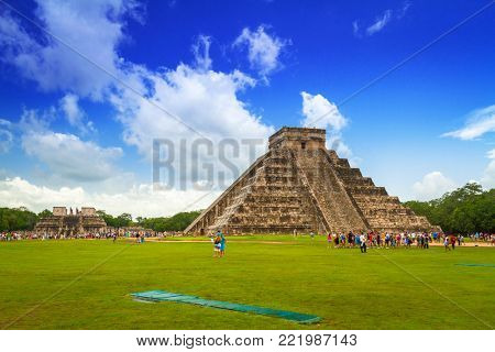 CHICHEN ITZA, MEXICO - JULY 12, 2011: Tourists visiting Kukulkan pyramid in Chichen Itza, Yucatan. Kukulkan pyramid is one of seven New World Wonders and popular tourist destination in Mexico.