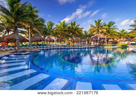 PLAYA DEL CARMEN, MEXICO - JULY 11, 2011: Luxury swimming pool scenery at RIU Yucatan Hotel in Playa del Carmen, Mexico. RIU Hotels & Resorts has more than 100 hotels in 19 countries.
