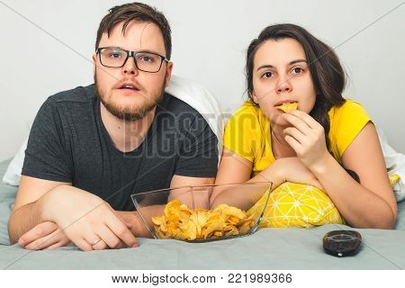 man with woman looking TV in bed with confused faces