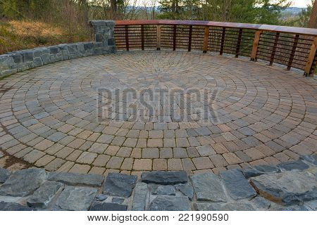 Garden Backyard circular brick stone pavers hardscape patio with wood railings stone wall landscaping