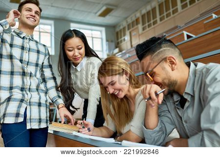Multi-ethnic group of students having fun  and laughing  in lecture hall of modern college while enjoying classes, focus on beautiful young woman