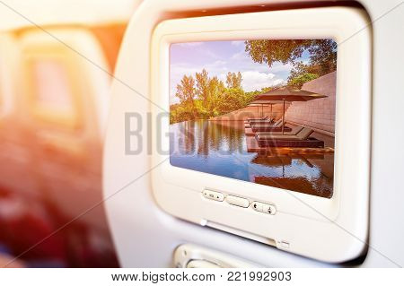 Aircraft In flight entertainment seat-back TV screens showing a picture of a swimming pool with daybeds in a luxury resort