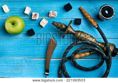 Tobacco background. Turkish smoking hookah with tobacco flavor of ripe green apple. Top view of a blue wooden background. Still life. Copy space. Flat lay