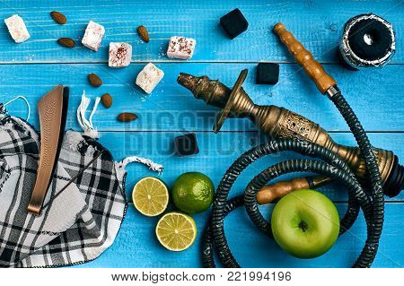 Tobacco background. Turkish smoking hookah with tobacco flavor of ripe green apple and lime. Top view of a blue wooden background. Still life. Copy space. Flat lay